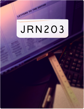 JRN 203 is written in black text, with a computer screen and a ruler rested on a keyboard in the background.