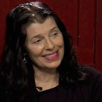 A photo of a person doing an interview with a red wall in the background.
