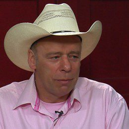 Carl Cosack, in a pink shirt and tan hat, doing an interview with a red wall in the background.