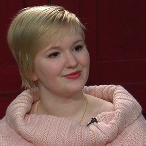 A person in a pink sweater doing an interview with a red wall in the background.