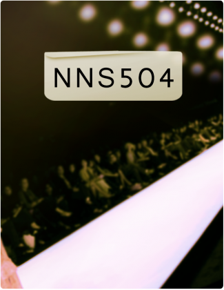 NNS 504 is written in black text, with a white runway, an audience and lights in the background.