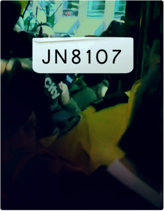 JN 8107 is written in black text, with reporters holding microphones in the background.