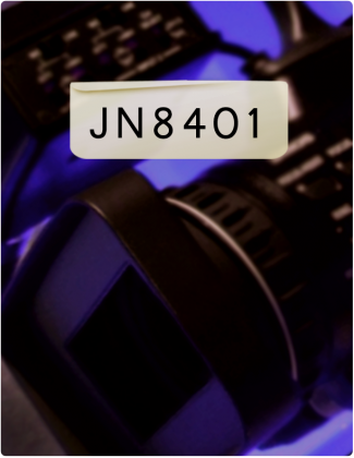 JN 8401 is written in black text with a blurry background, which includes a camera lens.