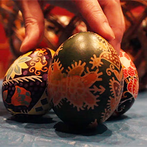 A close up photo of three decorative eggs, which are mainly black in colour with red patterns.