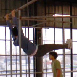 Someone swinging on an overhead bar, while another person walks by in the background.