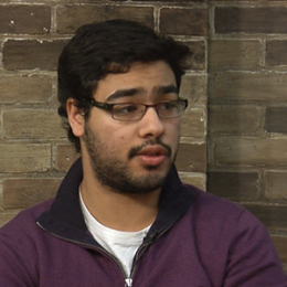 A photo of a person doing an interview with a brick wall in the background.